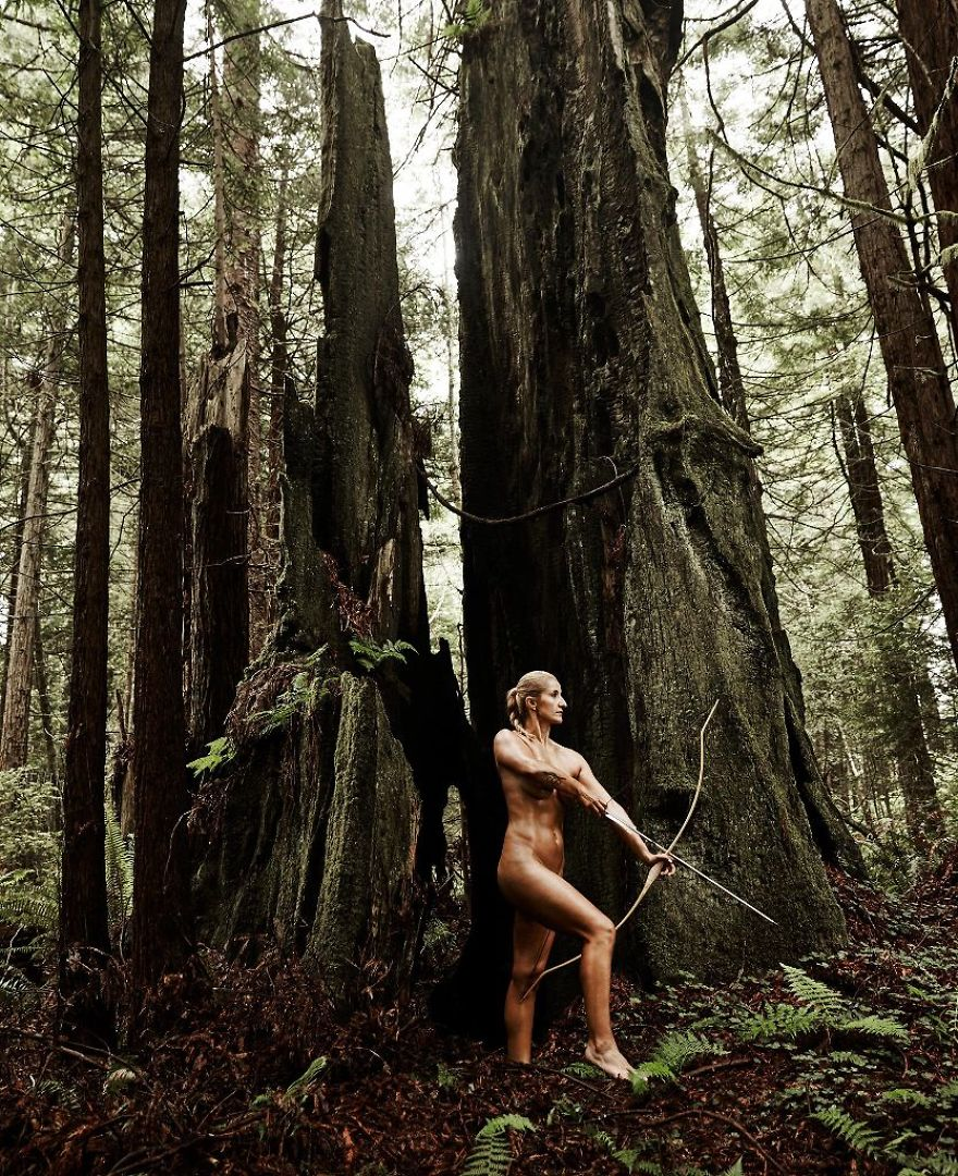 森林の中で弓を引くアーチェリー美女のヌード