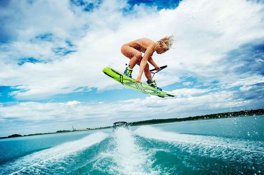 ボートサーフィンで格好良く回転ジャンプする金髪白人美女のヌード