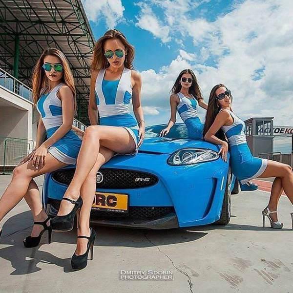 青空の下、ブルーの車をブルーのドレスで着飾るレースクイーン